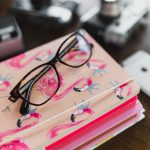 kaboompics_Corrective glasses on a stack of notebooks
